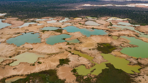 Shallow mining ponds dot the landscape in the La Pampa region of Madre de Dios, Peru. The colors of the ponds reflect suspended sediment and algae growth following the cessation of gold mining.